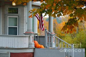 Pumpkins on a Vermont Porch in Autumn. A porch light and American flag welcome visitors.